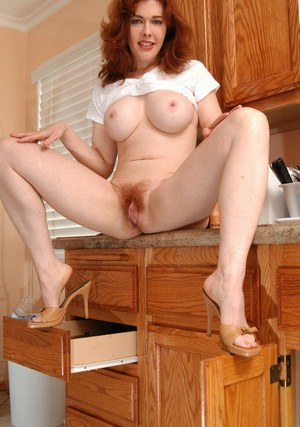 Busty redhead MILF getting horny and pleasing her hairy cunt with a big dildo