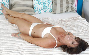 Older broad Mariana removing white bra and underwear to model naked on bed