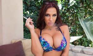 Smoking pornstar Lylith LaVey unleashing huge all natural tits outside