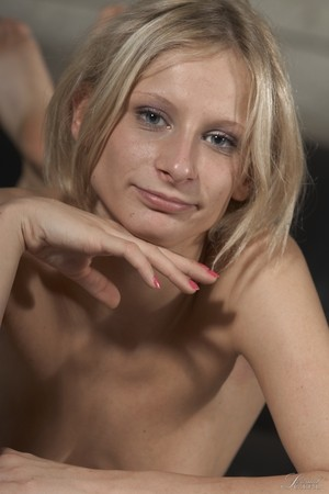 German lady Paris Pink poses nude and looks at the camera with her blue eyes