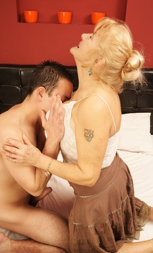 Old woman with glasses passionately fucked by a much younger guy on the bed