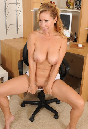 Hot older woman in a short skirt and glasses disrobes in her office