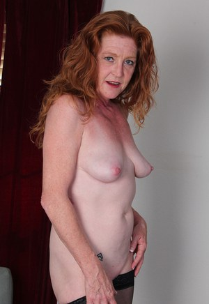 Mature redhead Tami Estelle displays her shaved pussy in black stockings