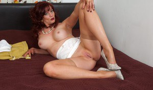 Hot redhead mature Holly Kiss spreading legs in sheer stockings on the bed