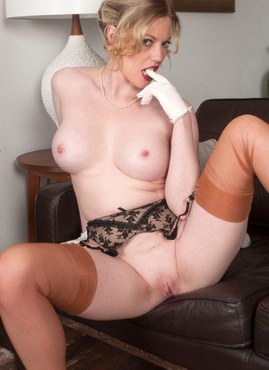 Older MILF Holly Kiss strips down to retro stockings and white gloves