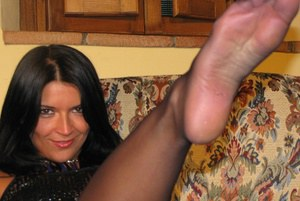 Dark haired female releases her hose attired feet from her heels