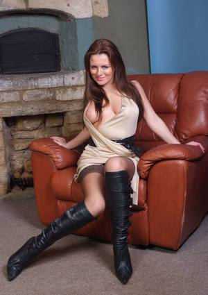 Clothed model in knee high leather boots has her tits fall free from her dress
