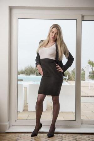 Busty beauty Tamara Grace sheds tight dress to pose in stockings by the window