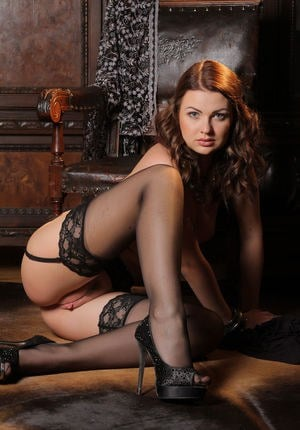 Long legged hot redhead Odara spreading to show naked upskirt wearing heels