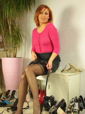 Hot redhead MILF Vixen Nylons flaunting firm boobs in ribboned black stockings