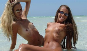Bikini and sunglasses clad lesbians get naked and lick pussy on tropical beach