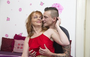 Mature redhead cheats on her husband with her toy boy on matrimonial bed