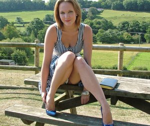 Clothed female shows off her blue stiletto heels on rural picnic table