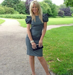 Clothed blonde woman shows off her legs in high heeled shoes on park path
