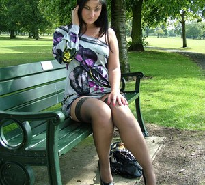 Dark haired girl flashes stocking tops while adjusting her pumps on a bench