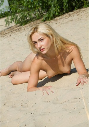 Skinny blonde bending over naked to show her puckered butt hole at the beach