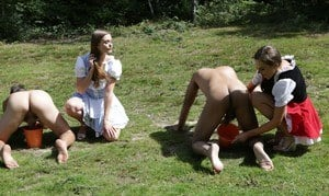 Horny femdom girls in costume head to the field to milk their naked man slave