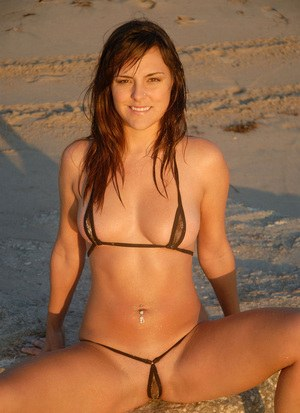 Hot sunbather Veronica in tiny skimpy bikini posing in the sand on her knees