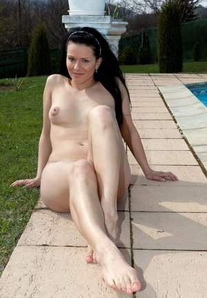 Dark haired solo girl Kylie models naked on the edge of a swimming pool