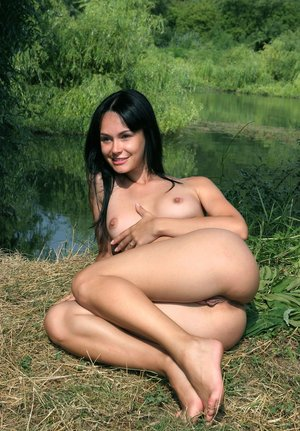 Skinny naked Olivia spreading legs under a tree for outdoor pussy closeup