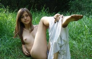 Carefree young teen shedding her sexy clothes to pose naked in the long grass