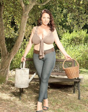 Hugely busty MILF Joana Bliss pauses to wet her massive juggs outdoors