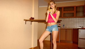 Cute young long legged amateur in denim shorts poses seductively while eating