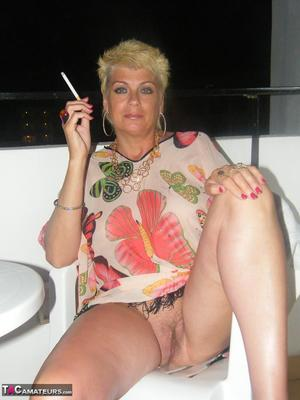 Mature MILF with blonde hair and big tits shows her twat while having a smoke