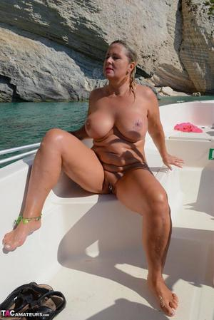 Busty blonde Chrissy pilots her speed boat nude to sun her thick naked body