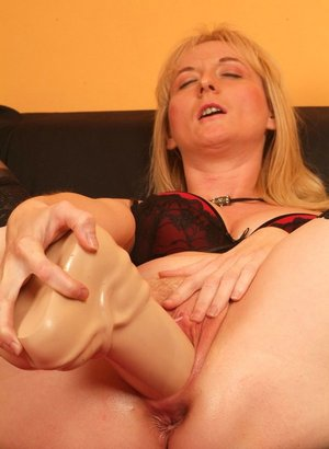 Older woman with blonde hair works a big dildo into her horny pussy