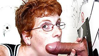 Mature redhead sucks dick through a gloryhole