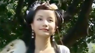Beautiful Chinese Girl Walks Through A Garden