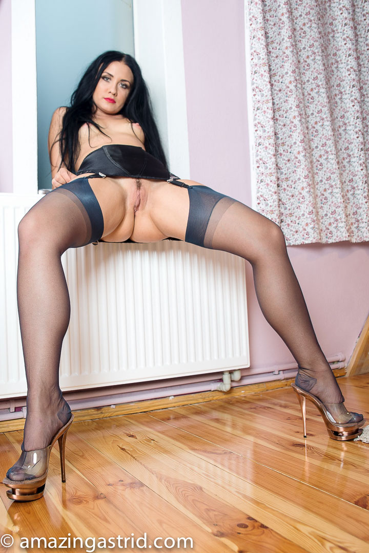 Dark haired fet model Amazing Astrid inserting sex toy wearing black nylons