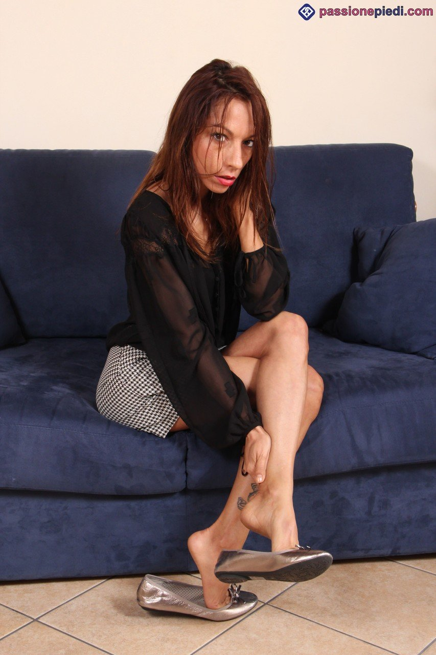 Slender female Jessica frees her pretty feet from flat shoes in a short skirt