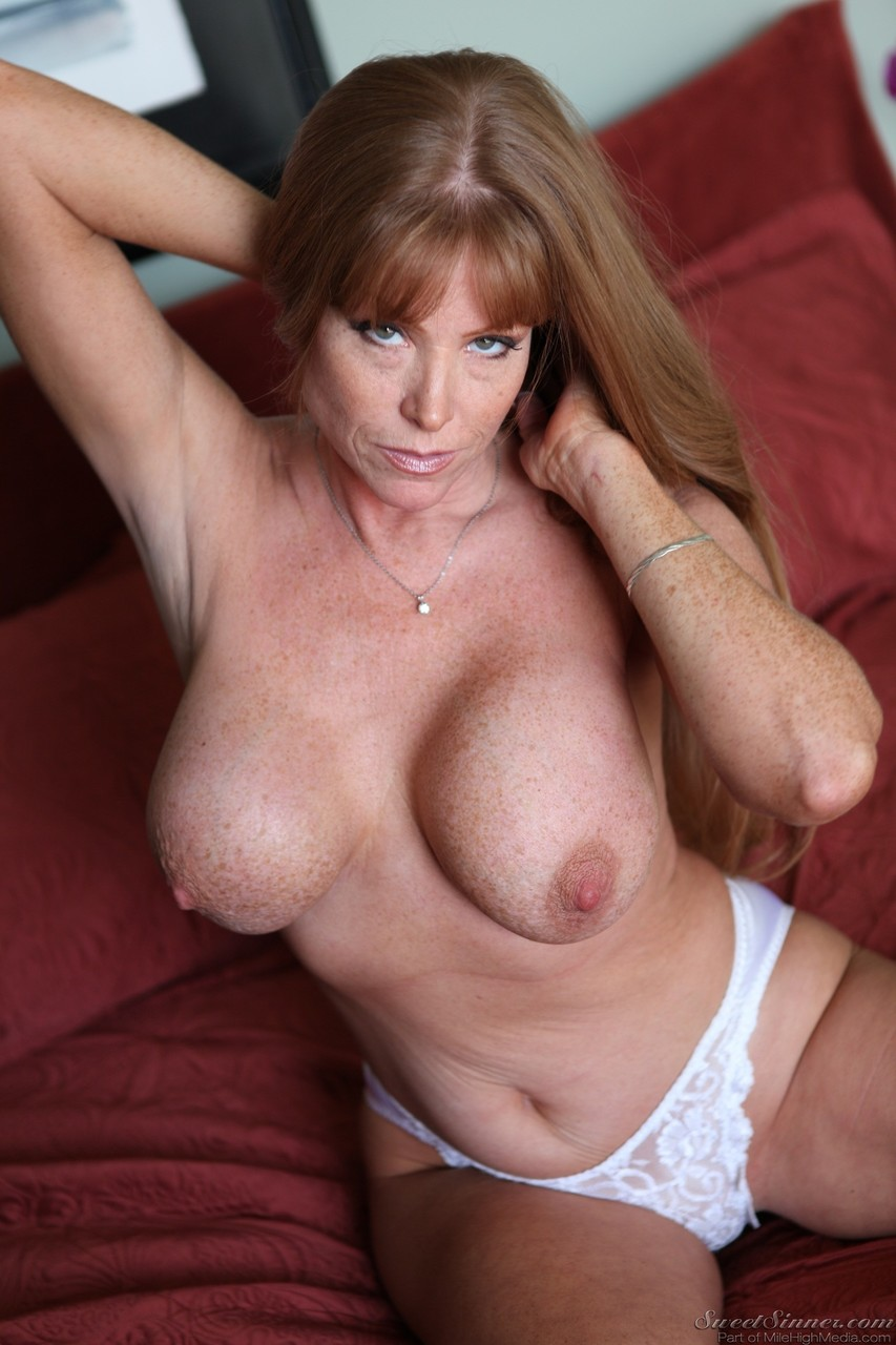 American mature model Darla Crane flaunts her fake tits on the couch