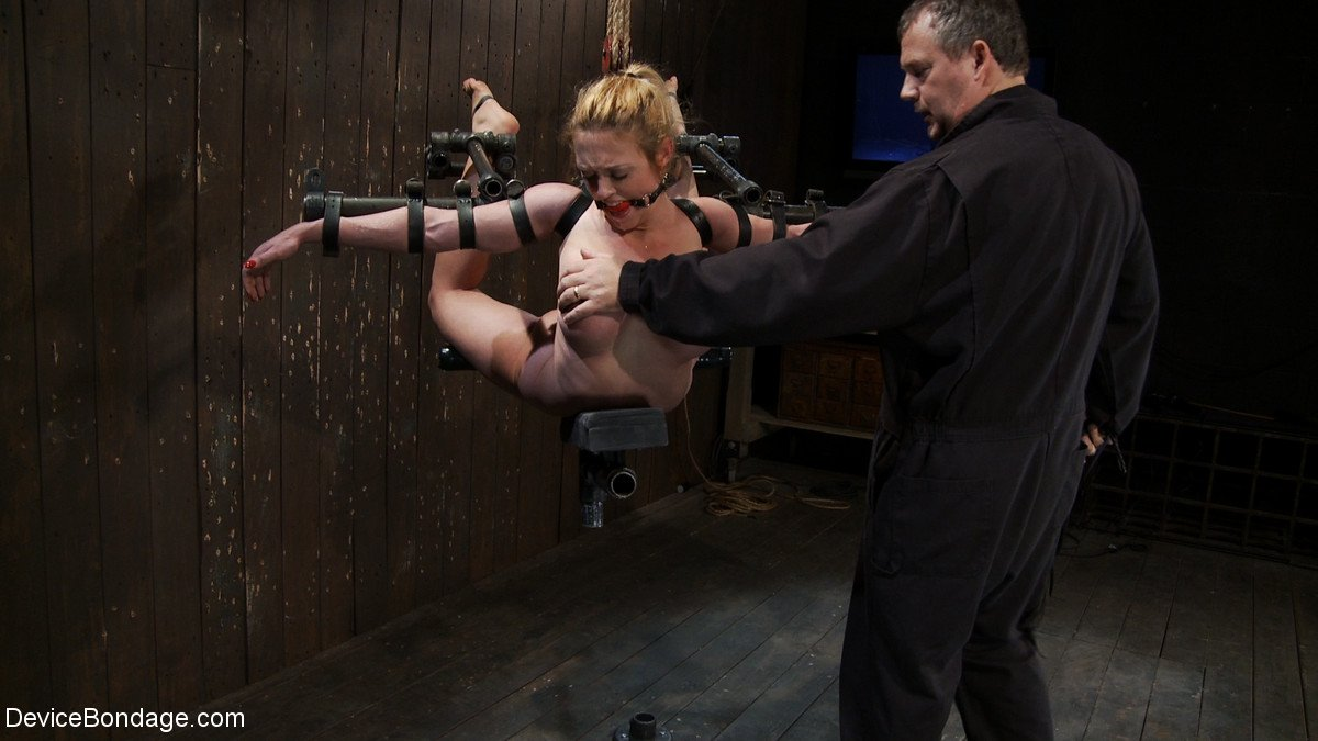 Busty Dee Williams gets tied to a custom metal suspension piece tortured