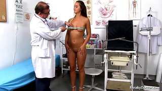Nude brunette is spreading her legs wide open for a good fuck in a gyno office