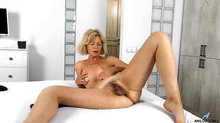 Mature babe with a bush masturbates solo in bed