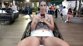 Lady in a hat without panties under a skirt in a shopping center