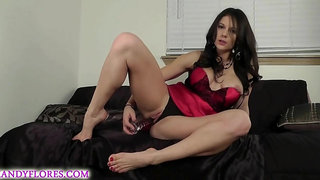 Busty brunette in a satin dress is posing and toying her pussy from the back