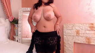 Busty MILF slowly undresses her huge tits on cam