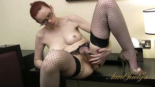 Mistique masturbates her mature pussy in the office.