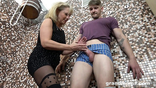 Old woman gives a blowjob and tugjob to young guy in the sauna