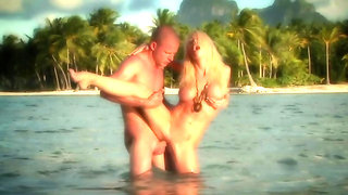 Man fools around with blonde's mouth and cunt in the ocean