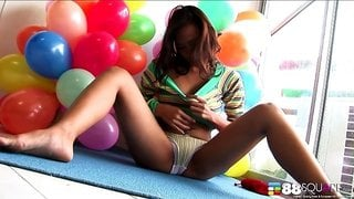 Busty Asian sits in a pile of balloons and toys her vagina