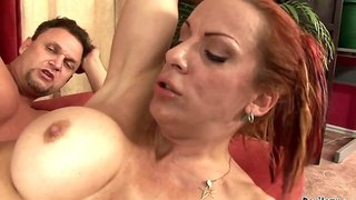 A redhead is placing her mouth around a cock to suck it right